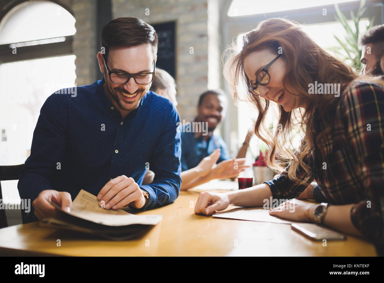 Flirting coworkers eating out and dating in restaurant - Stock Image
