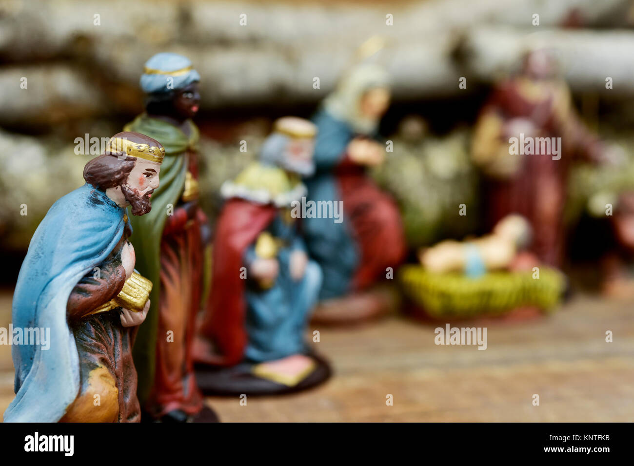 closeup of the three kings carrying their gifts adoring the Child Jesus on a rustic nativity scene - Stock Image