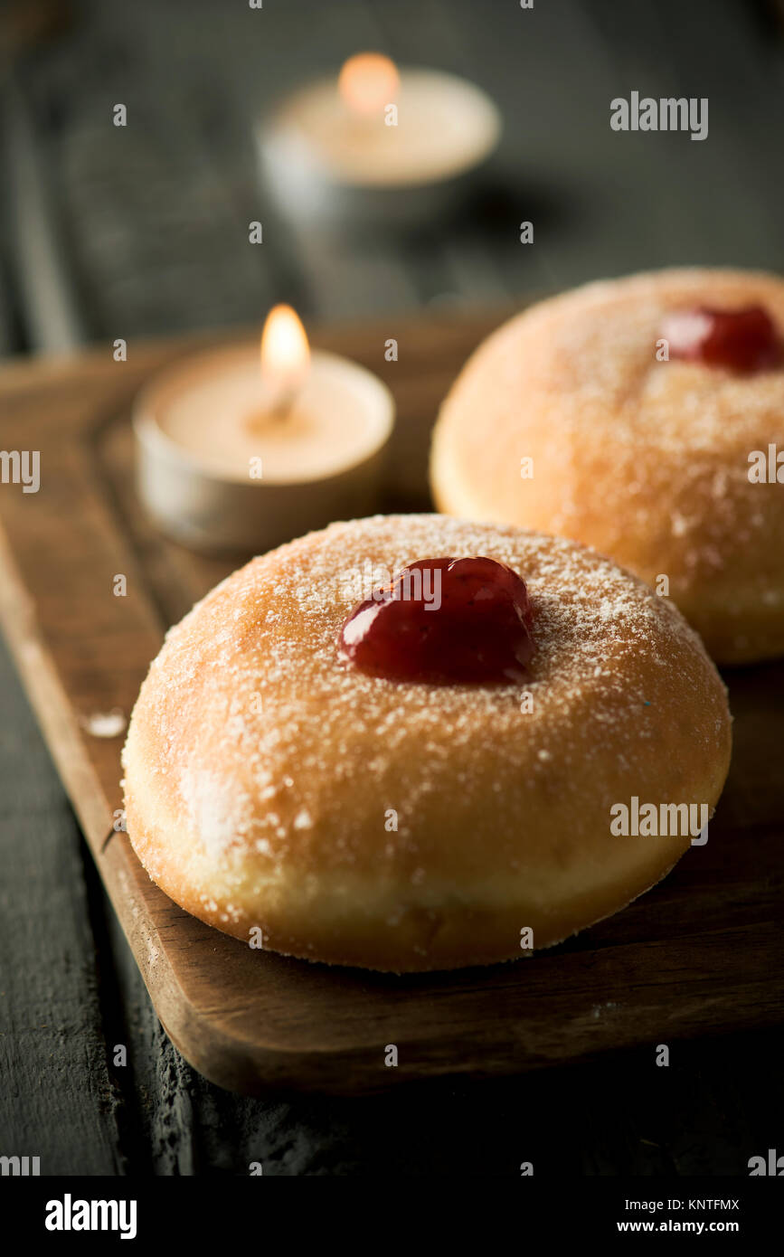 closeup of some sufganiyot, Jewish donuts filled with strawberry jelly traditionally eaten on Hanukkah, and some - Stock Image