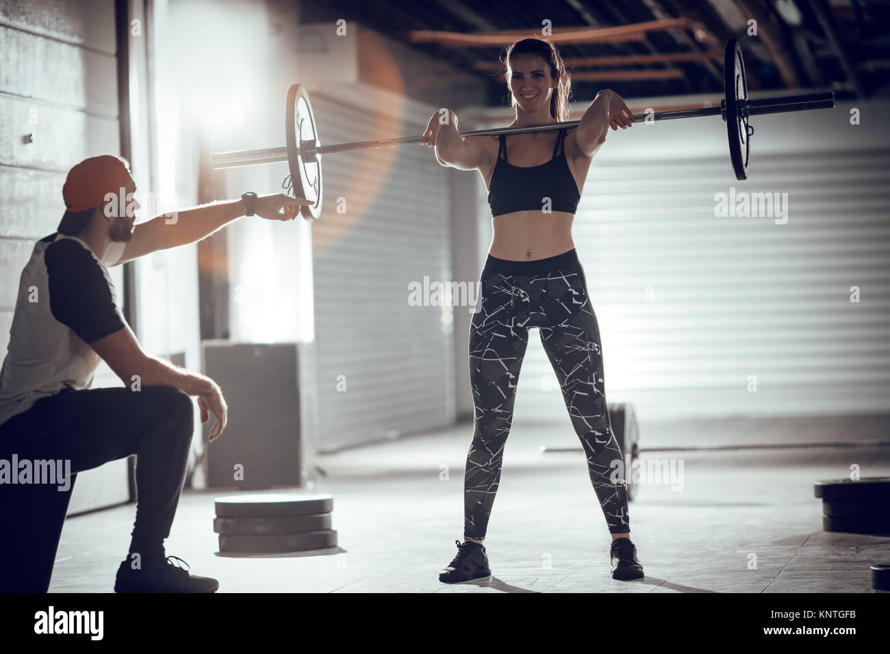Young muscular woman doing cross workout with a personal trainer at