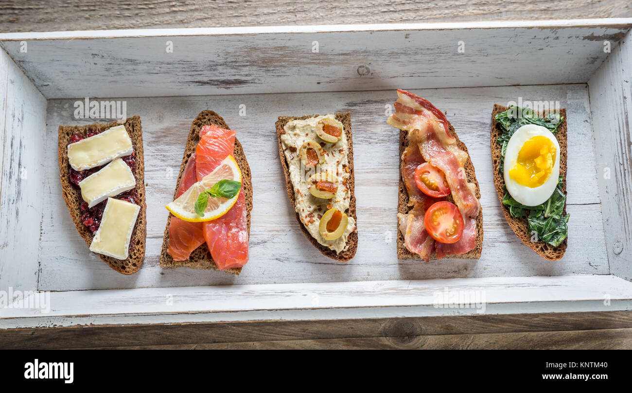 Bruschetta with different toppings on the wooden tray Stock Photo
