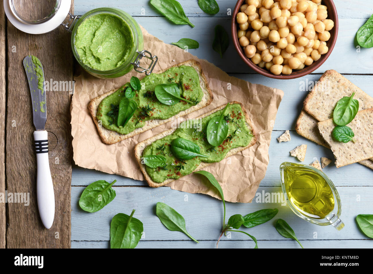 Two crackers with green spinach humus - Stock Image