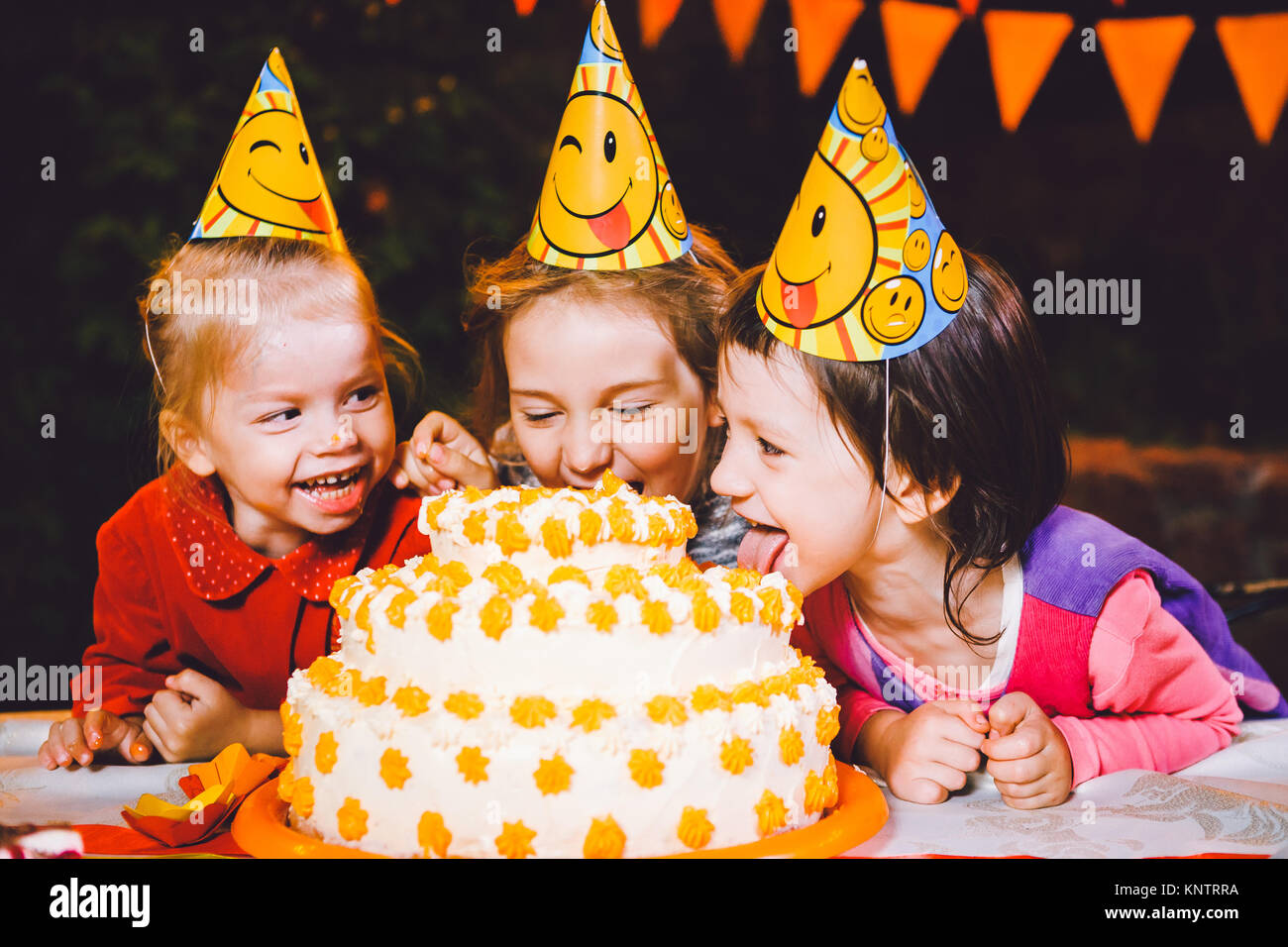 Children's birthday party. Three cheerful children girls at the table eating cake with their hands and smearing - Stock Image