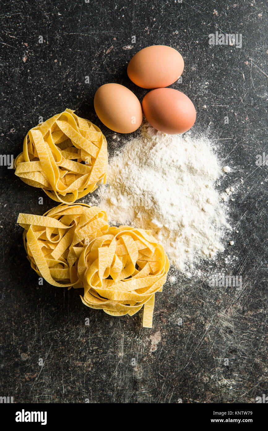 Raw tagliatelle pasta, flour and eggs. - Stock Image
