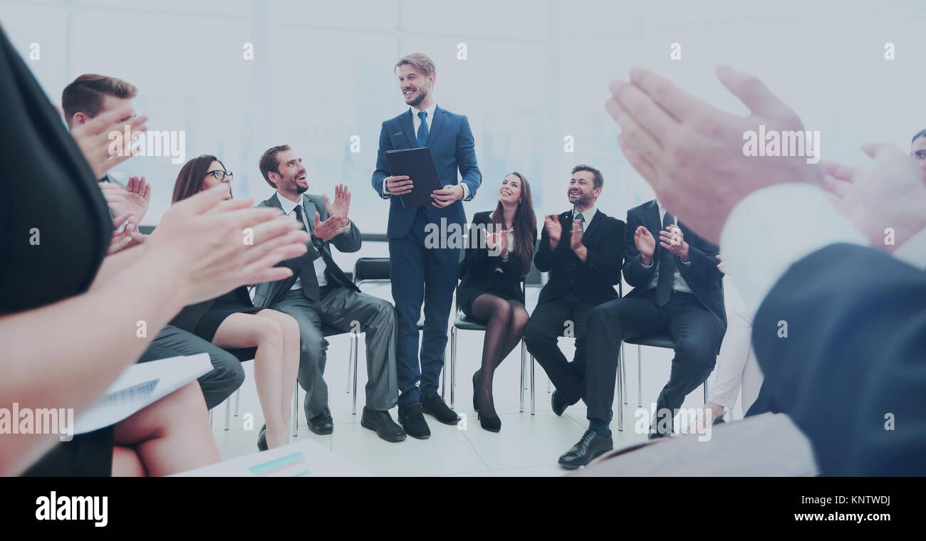 Business group greets leader with clapping and smiling - Stock Image