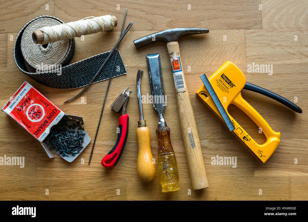Variety of tools and materials for upholstery work, including hammer, chisel, tack lifter, staple lifter, webbing, - Stock Image