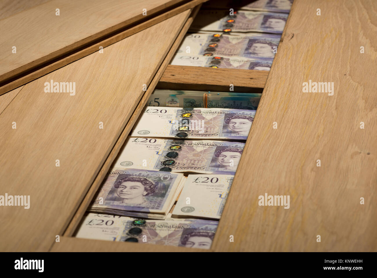 Poor interest bank rates, money £5 £20 hidden under oak wooden floor boards as alternative to safety deposit concealed Stock Photo