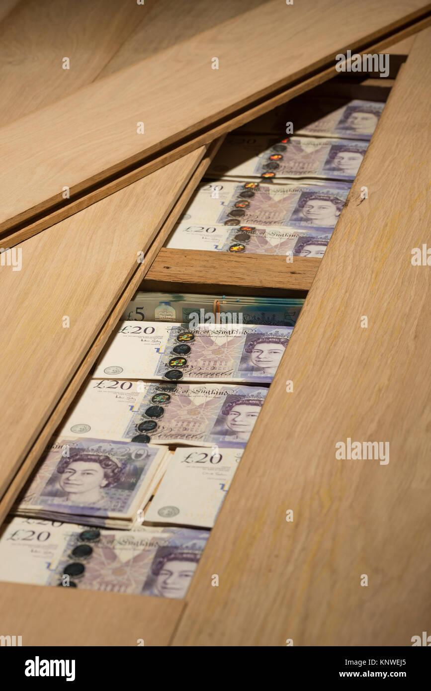 Poor interest bank rates, money £5 £20 hidden under oak wooden floor boards as alternative to safety deposit - Stock Image