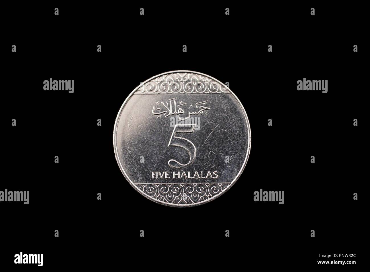 A super macro image of a Saudi Arabian 5 halalas coin isolated on a black background - Stock Image