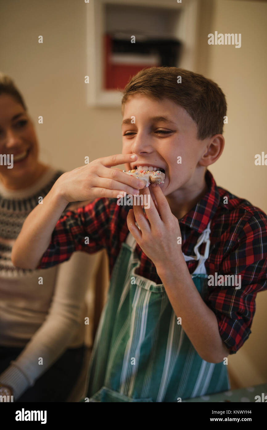 Little boy is tucking in to a homemade christmas biscuit. - Stock Image