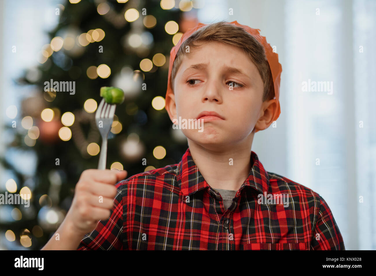 Little boy is holding a brussel sprout on his fork at christmas time. He is wearing a party hat and is grimacing - Stock Image