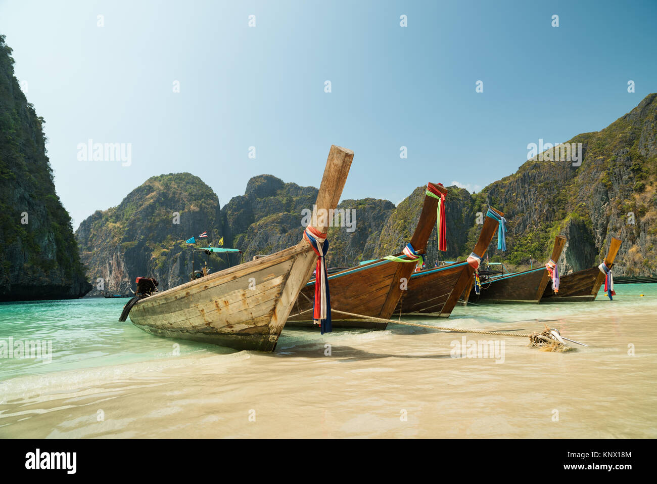 Longtail boats anchored at Maya Bay on Phi Phi Leh Island, Krabi Province, Thailand. It is part of Mu Ko Phi Phi Stock Photo