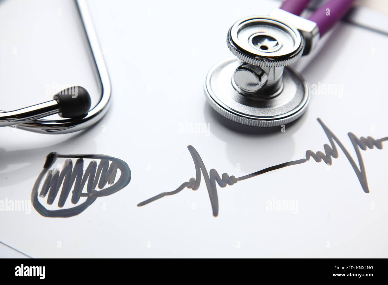 Medical stethoscope with cardiogram lying on desk in hospital - Stock Image