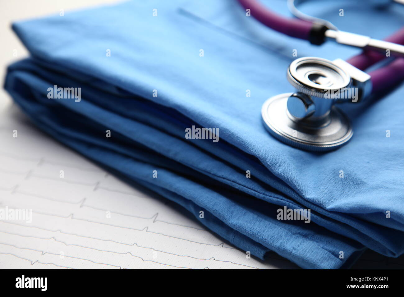 Doctor coat with medical stethoscope on the desk - Stock Image