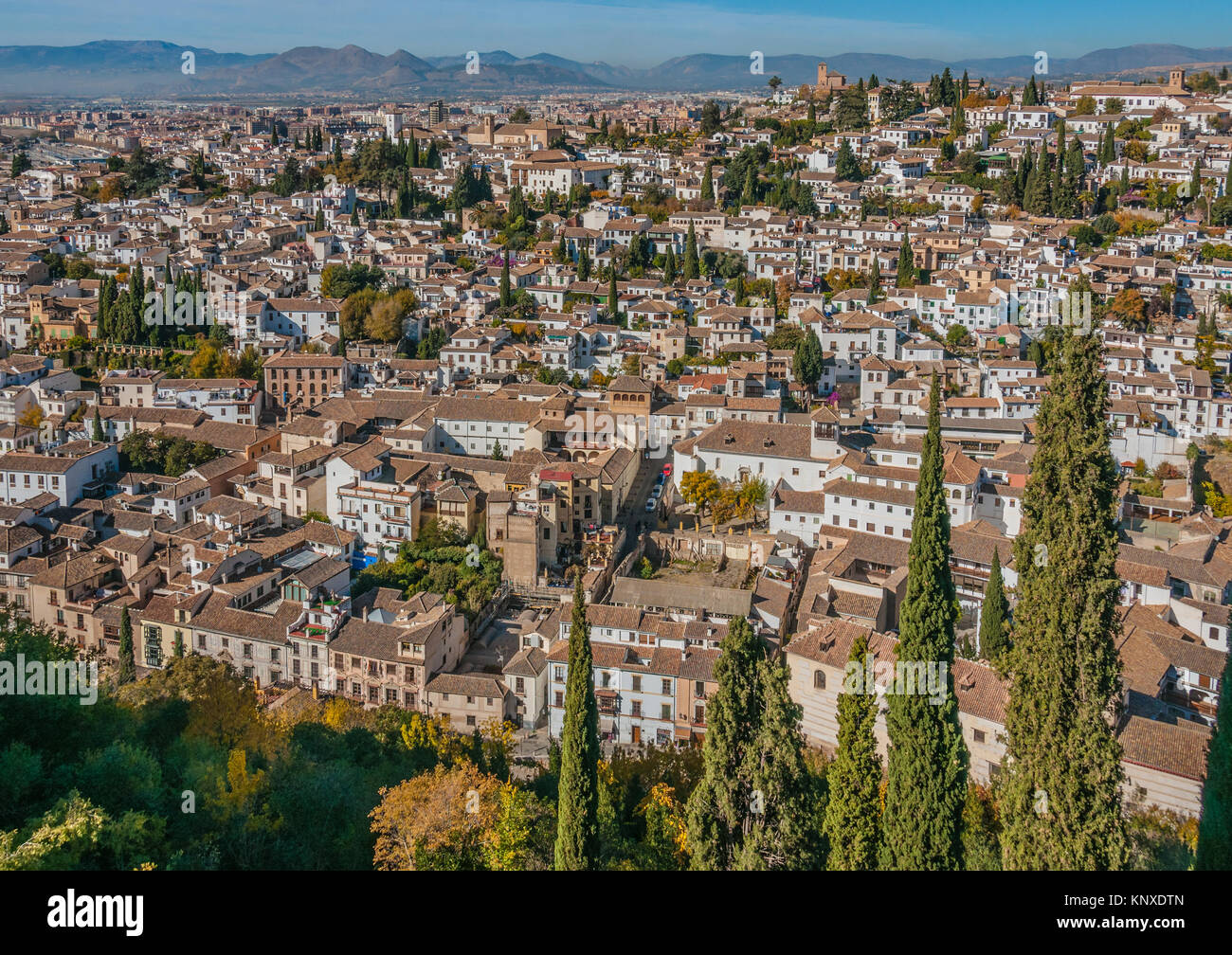 A view to the old Moorish part of Granada. White houses with brown tiled roofs, brown churches, green cypress trees - Stock Image