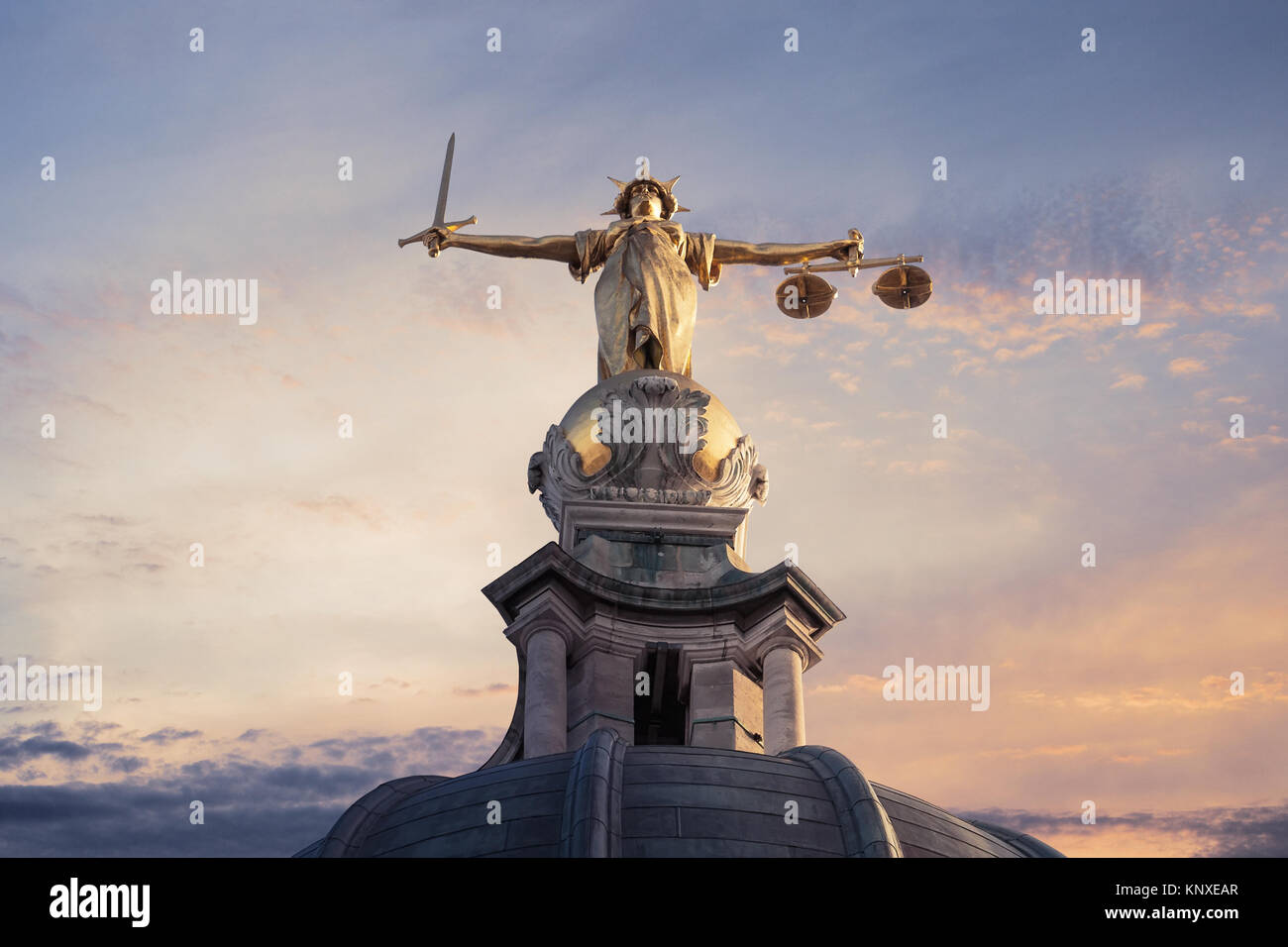 Gold Lady Justice Statue on the top of the Old Bailey in London, England, with a sunset sky in the background - Stock Image