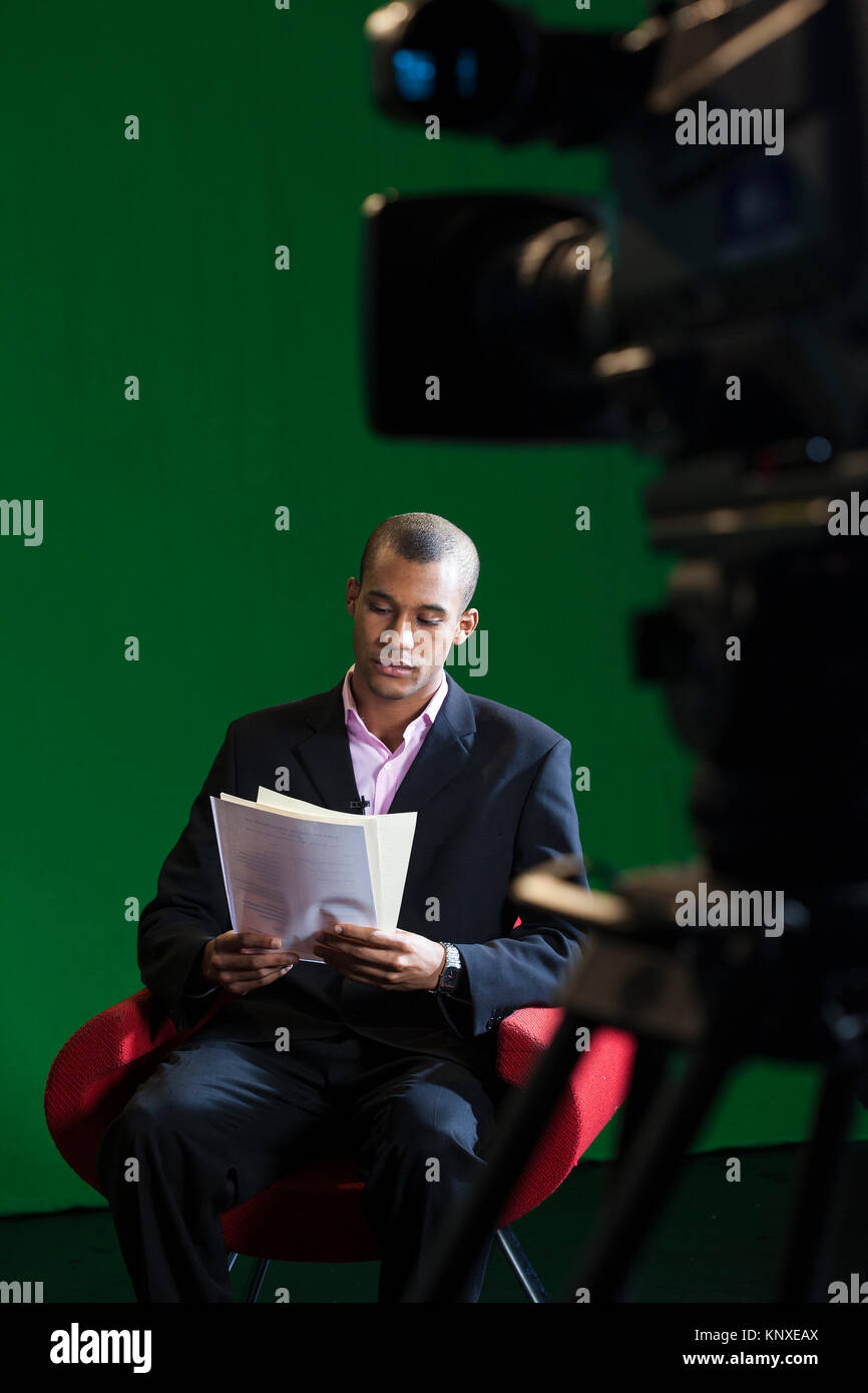 A male television presenter sits alone, reading through scripts before a recording in a green screen TV Studio - Stock Image