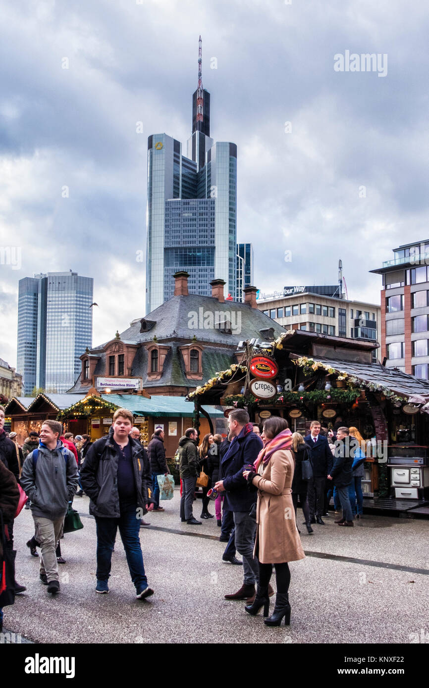 Germany,Frankfurt,People enjoy German market stalls in front of old Hauptwache building with new Commerzbank Tower Stock Photo