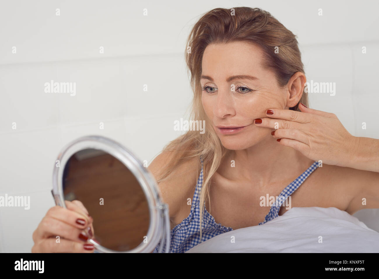 Portrait of a worried woman thinking of aging while looking in the mirror at her face and her facial wrinkles - Stock Image