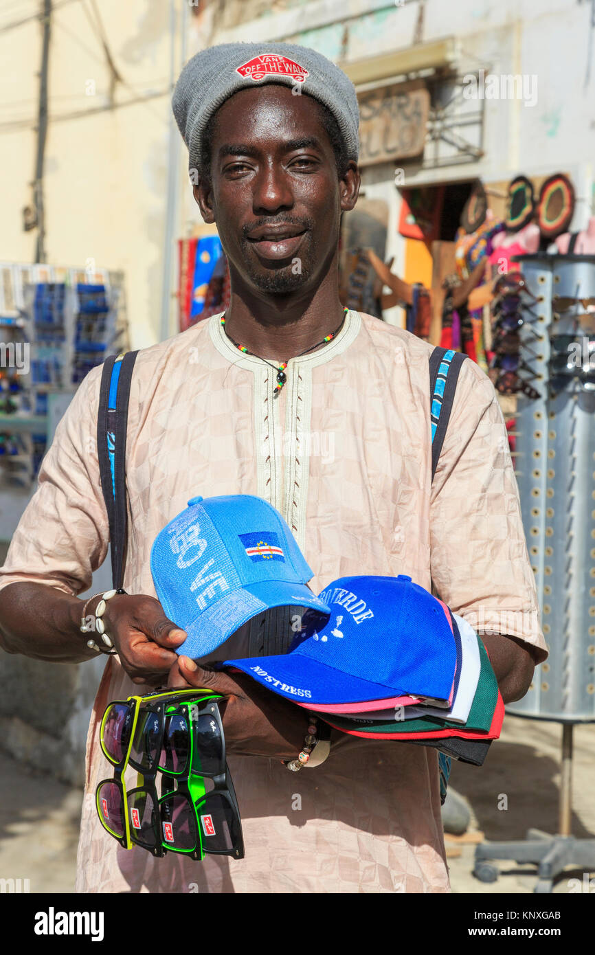 Man from Senegal selling baseball hats embossed with Cape Verde logo and fake Ray Ban sunglasses at the tourists - Stock Image