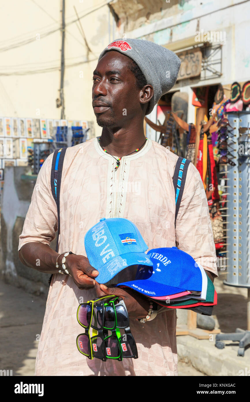 Man from Senegal selling baseball hats embossed with the Cape Verde logo and fake Ray Ban sunglasses at the tourist - Stock Image