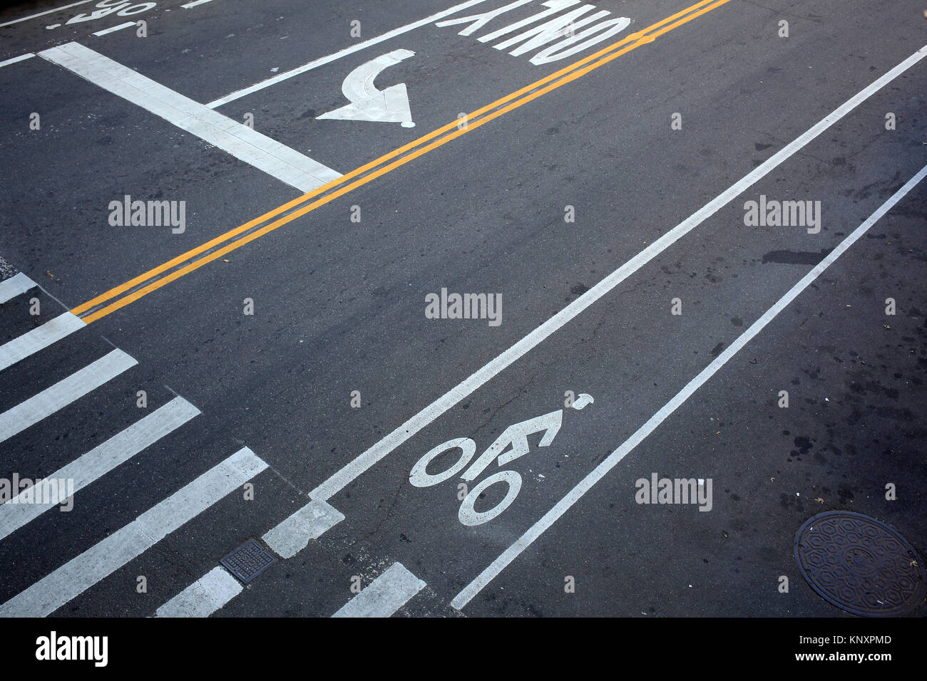 looking down on street traffic markings at New York City intersection - Stock Image
