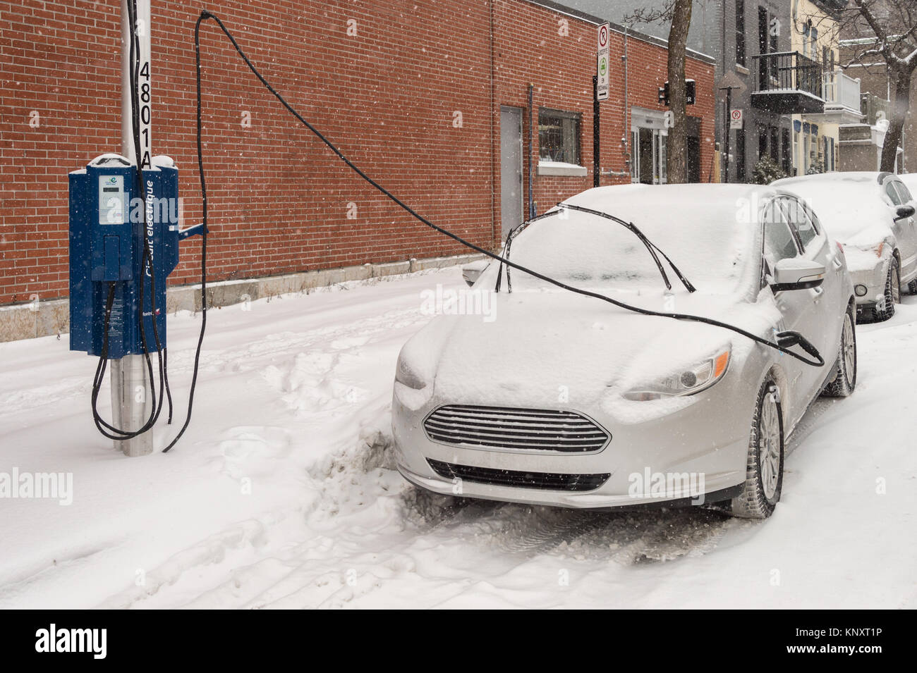 Montreal, Canada - 12 December 2017: Electric car getting charged in Montreal during snowstorm - Stock Image