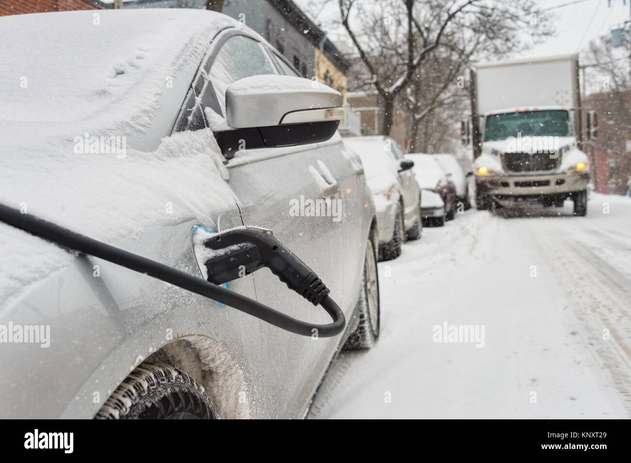 Electric car getting charged in Montreal during snowstorm - Stock Image