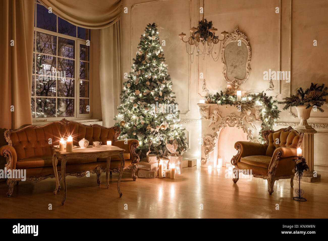 Christmas evening by candlelight. classic apartments with a white fireplace, decorated tree, sofa, large windows Stock Photo
