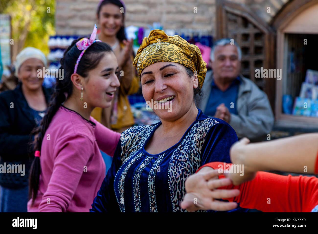 Uzbek Women Dancing In The Street, Khiva, Uzbekistan Stock Photo
