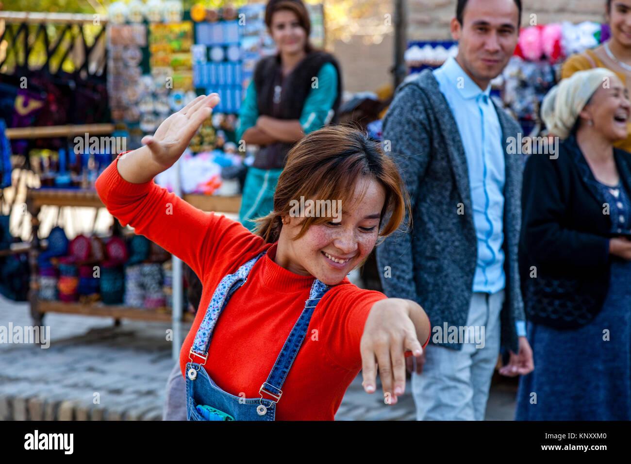 A Young Uzbek Woman Dancing In The Street, Khiva, Uzbekistan Stock Photo