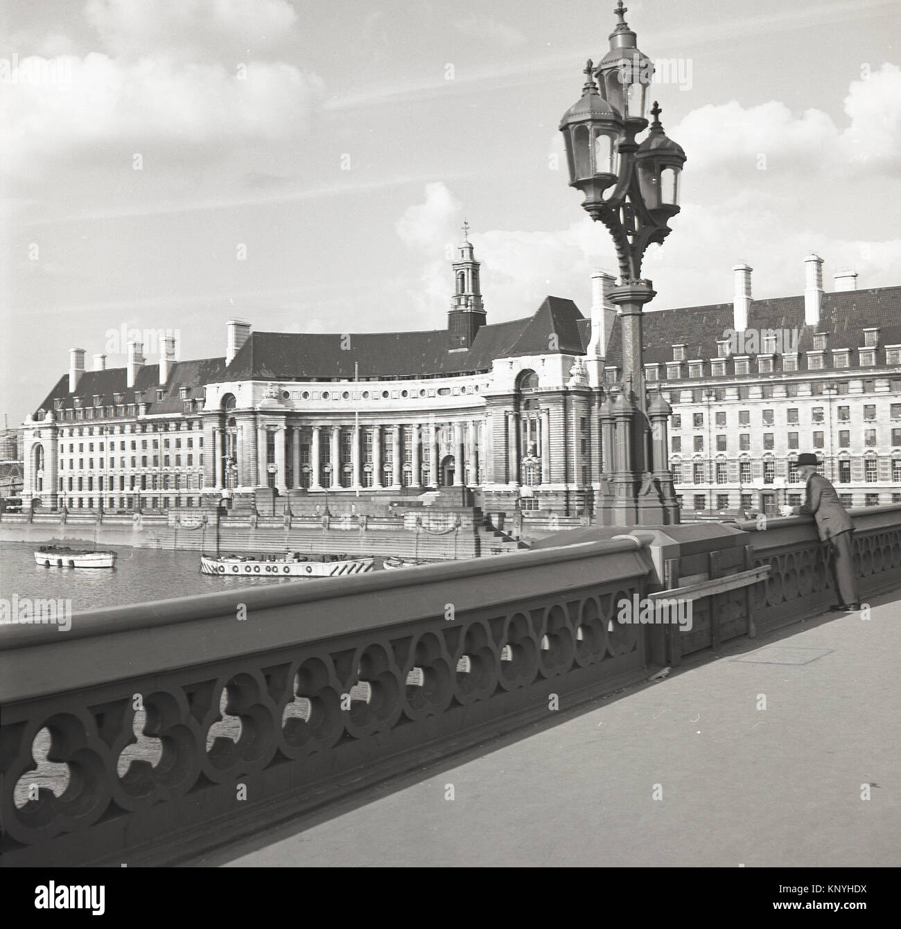 1950s, historical, man standing on Westminster Bridge, London, looking down the River Thames and with the impressive - Stock Image
