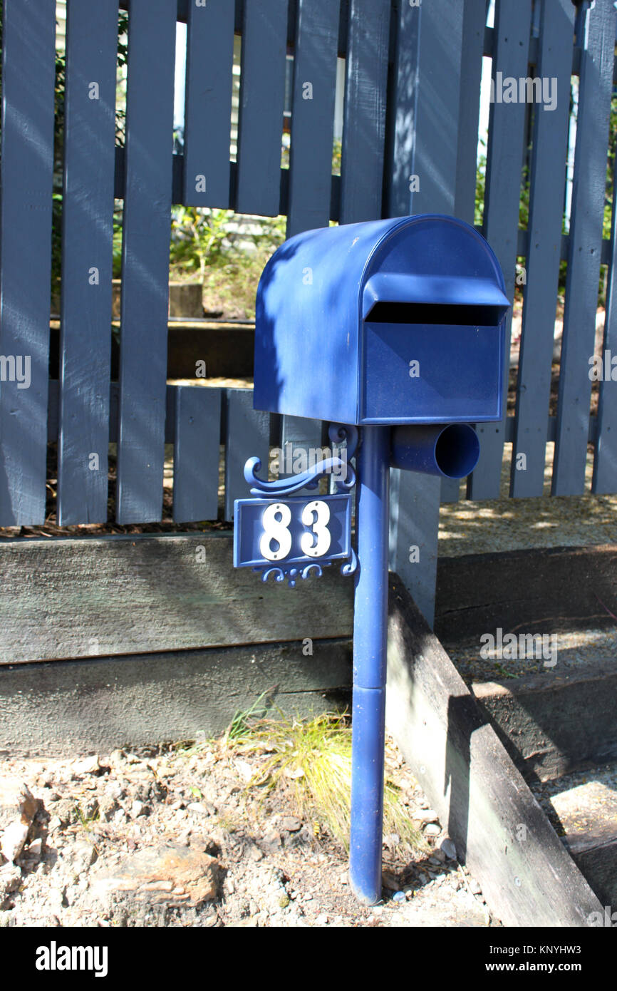 Blue Mailbox in Brisbane Australia With Hole Cut in Fence for Retreiving Mail - Stock Image