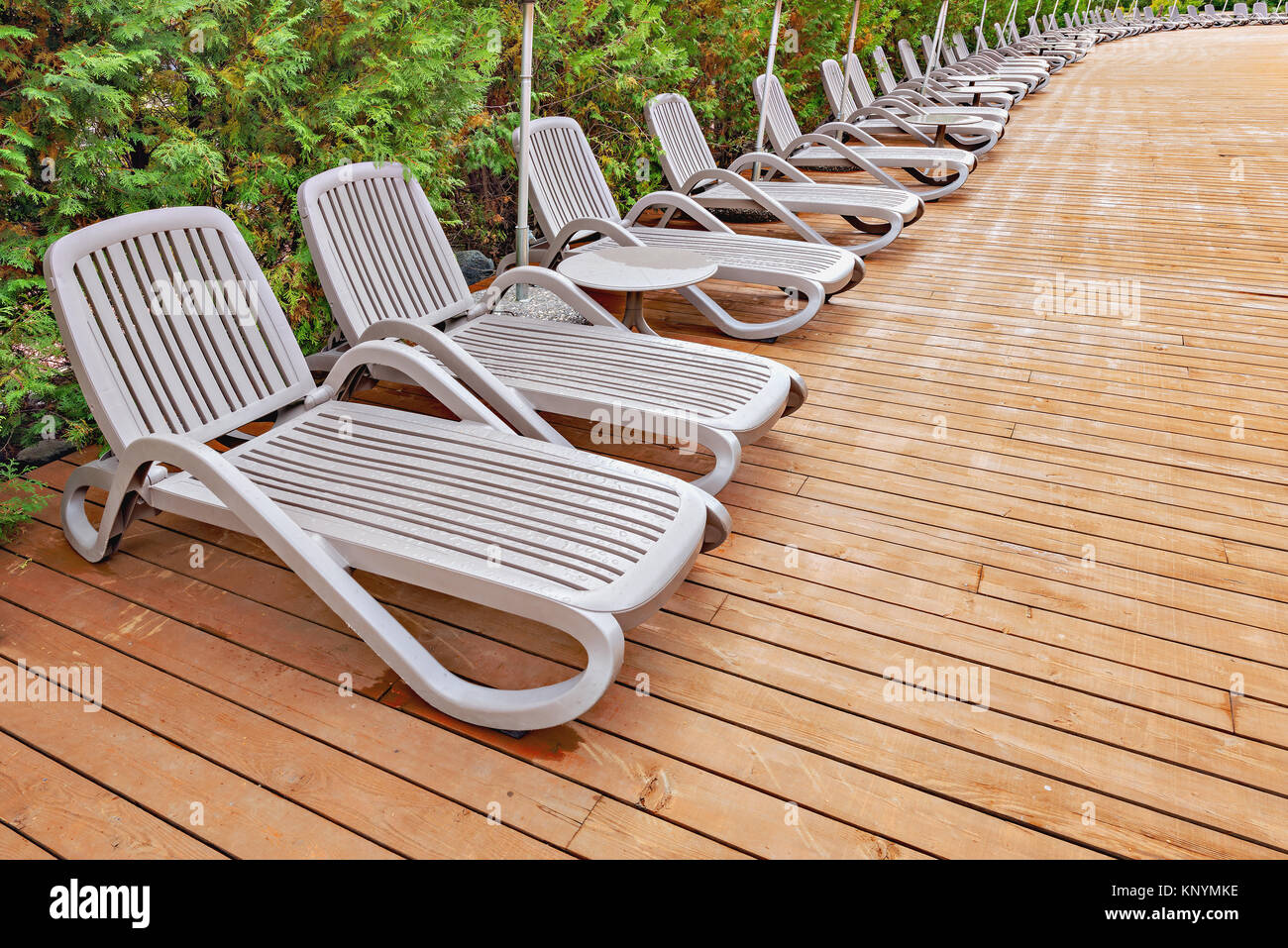 Many chaise-longues by the swimming pool on the hotel territory. - Stock Image