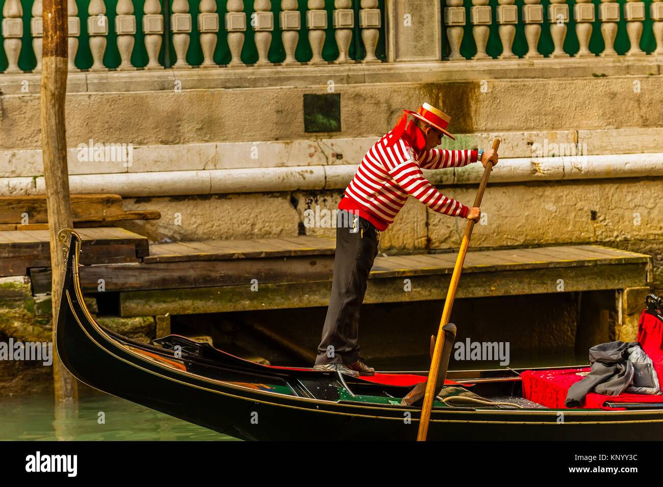A gondolier rowing on a back canal, Venice, Italy. - Stock Image