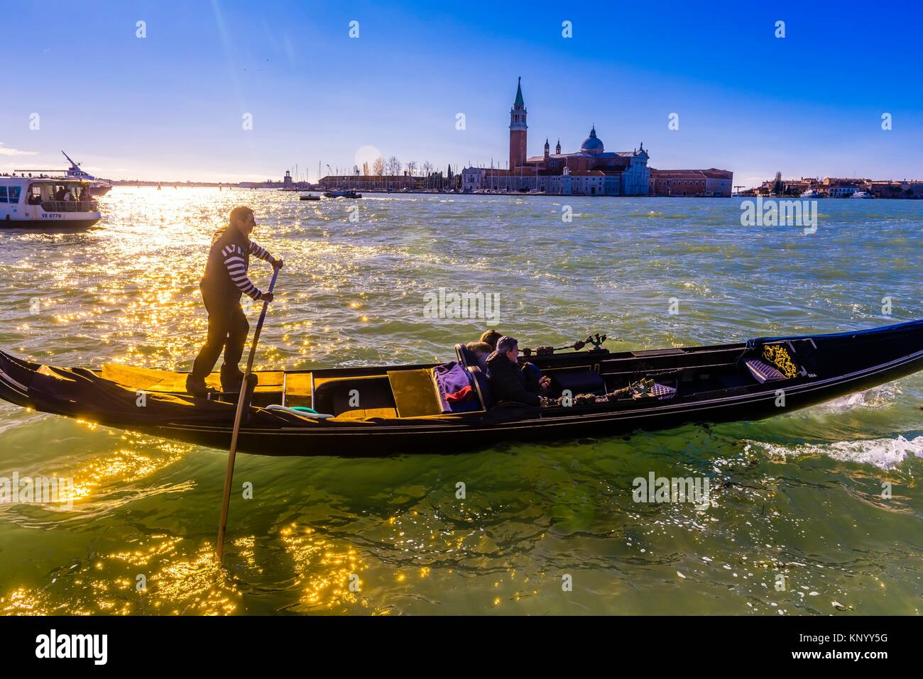 Gondolier rowing on the Venice Lagoon with Church of San Giorgio Maggiore in background, Venice, Italy. - Stock Image