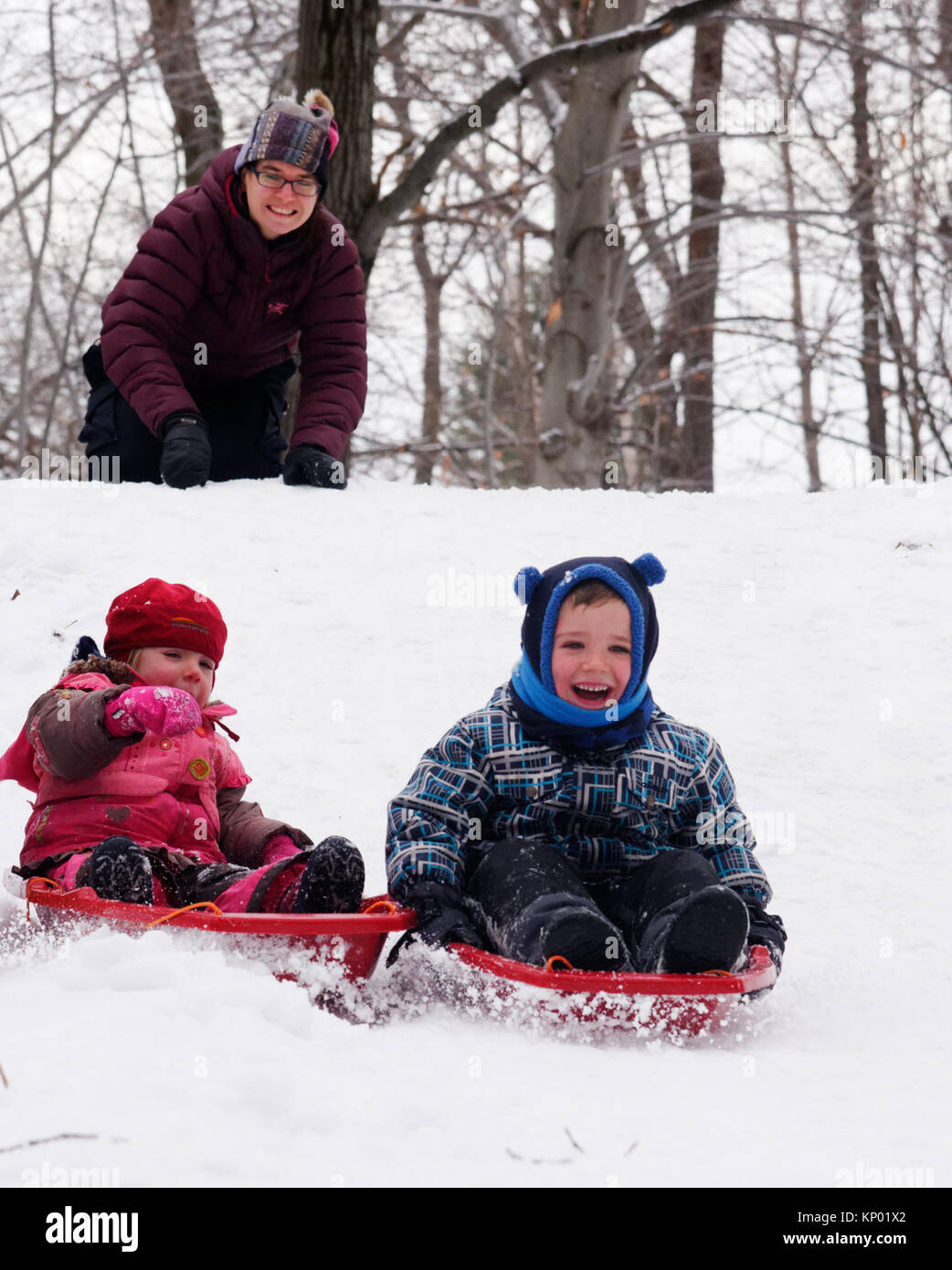 Brother and sisters (5 and 3 yrs old) sledging together in Quebec in winter, while mum looks on - Stock Image