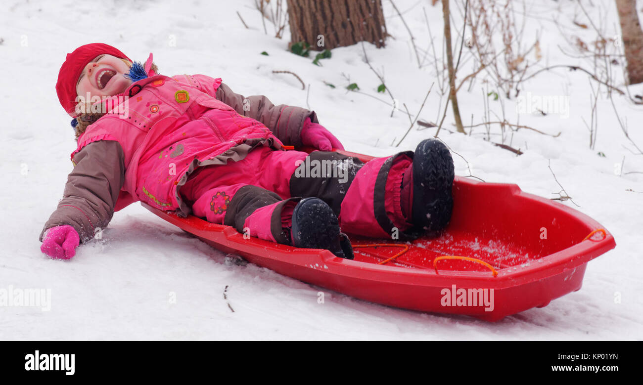 A little girl (3 yr old) sledging in Quebec - Stock Image