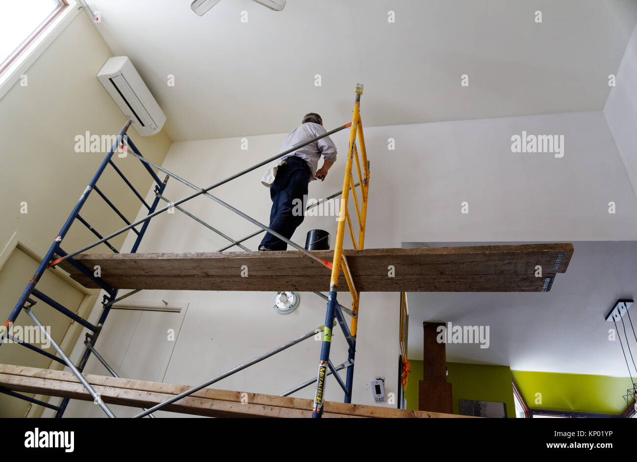 A decorator painting a house interior, difficult access involving scaffolding - Stock Image