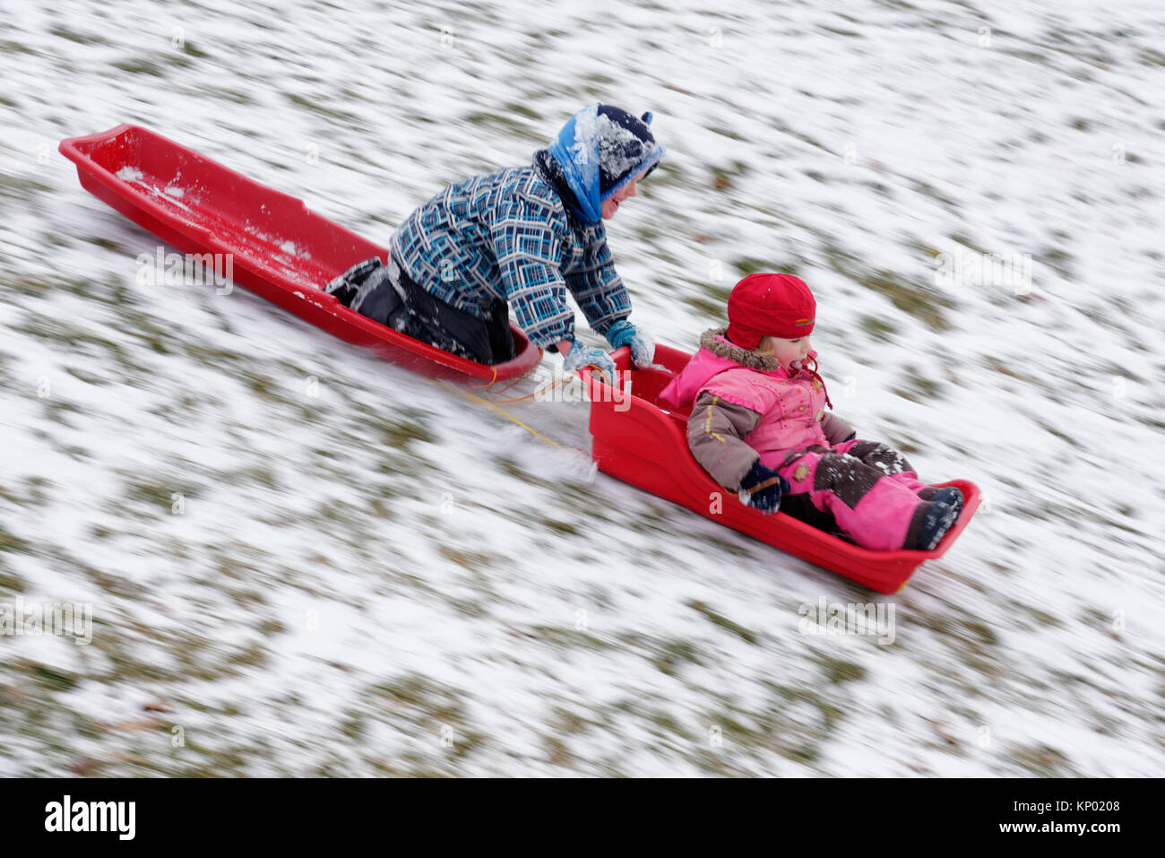 Brother and sister (5 and 3 yrs old) sledging together in Quebec City Stock Photo