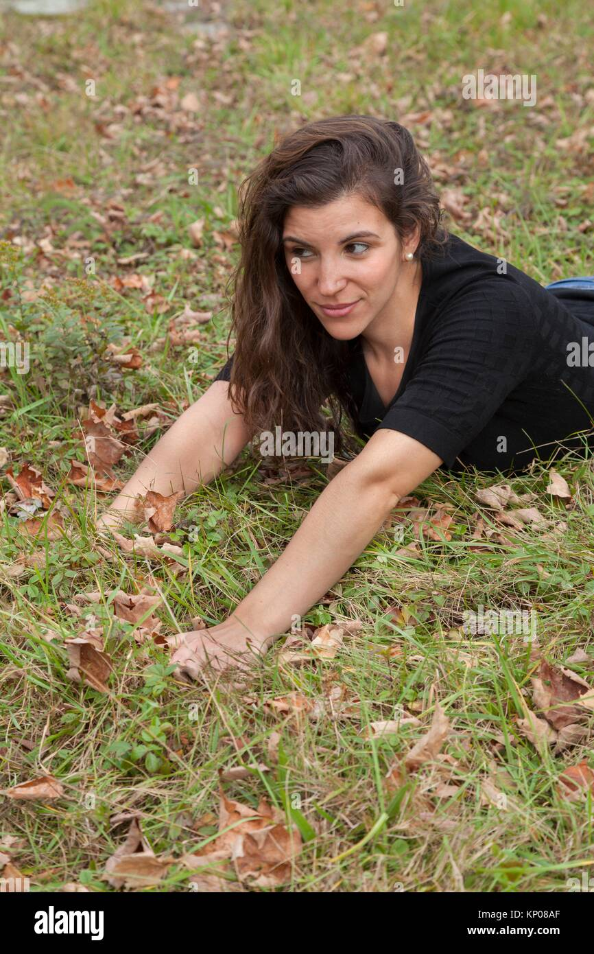 Young woman leaning on the grass among dead leaves. - Stock Image