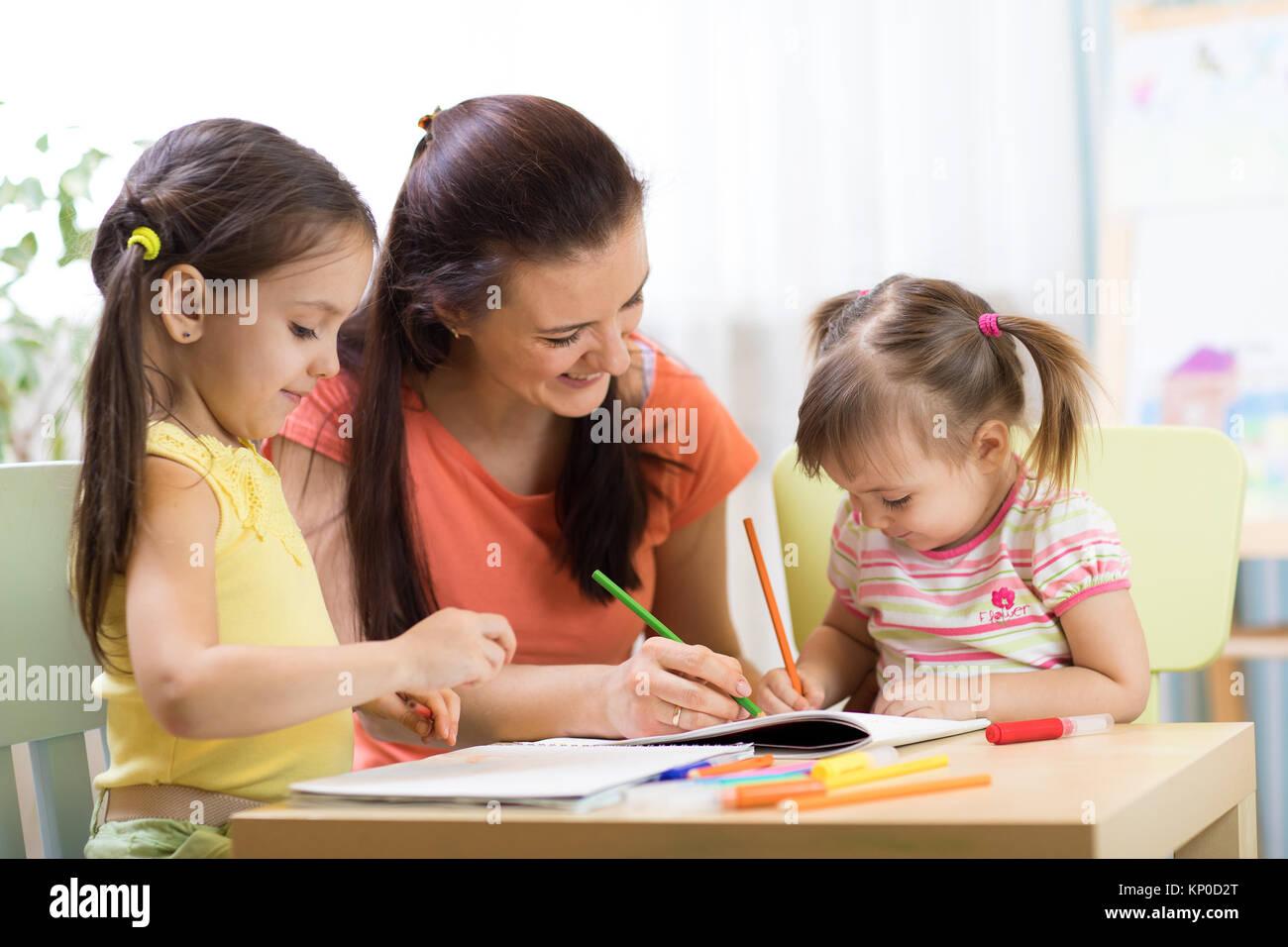 Teacher mom working with creative kids - Stock Image