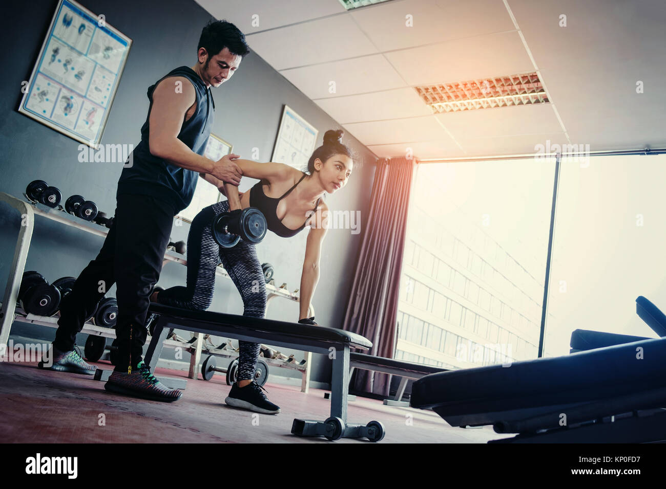 Sport girl doing weight exercises working with heavy dumbbells her personal trainer at Gym workout - Stock Image