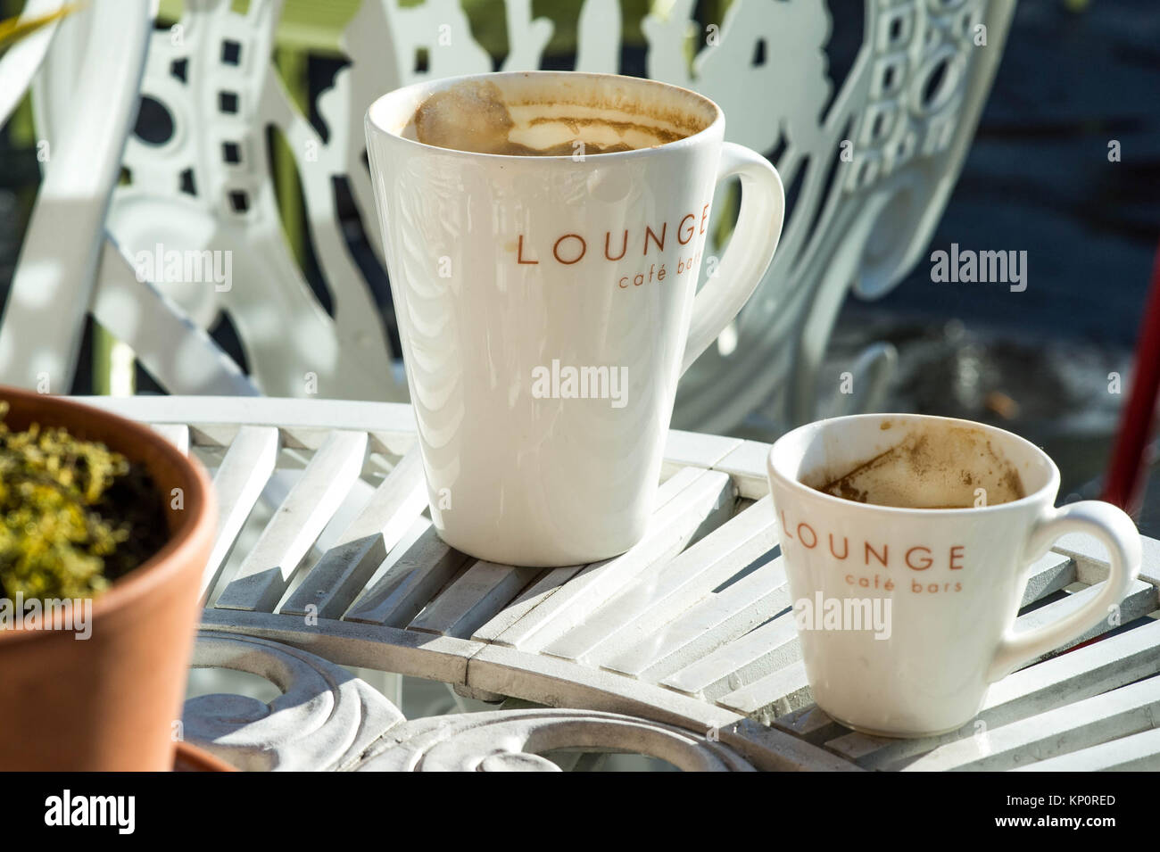 Mug of Coffee on a White Iron Outside Table Top In a Restaurant or a Garden - Stock Image