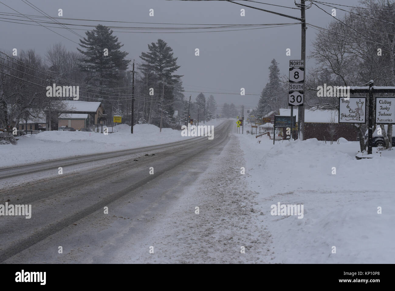Slippery snow covered road in Speculator, NY New York, USA in the Adirondack Mountains with no people or vehicles - Stock Image