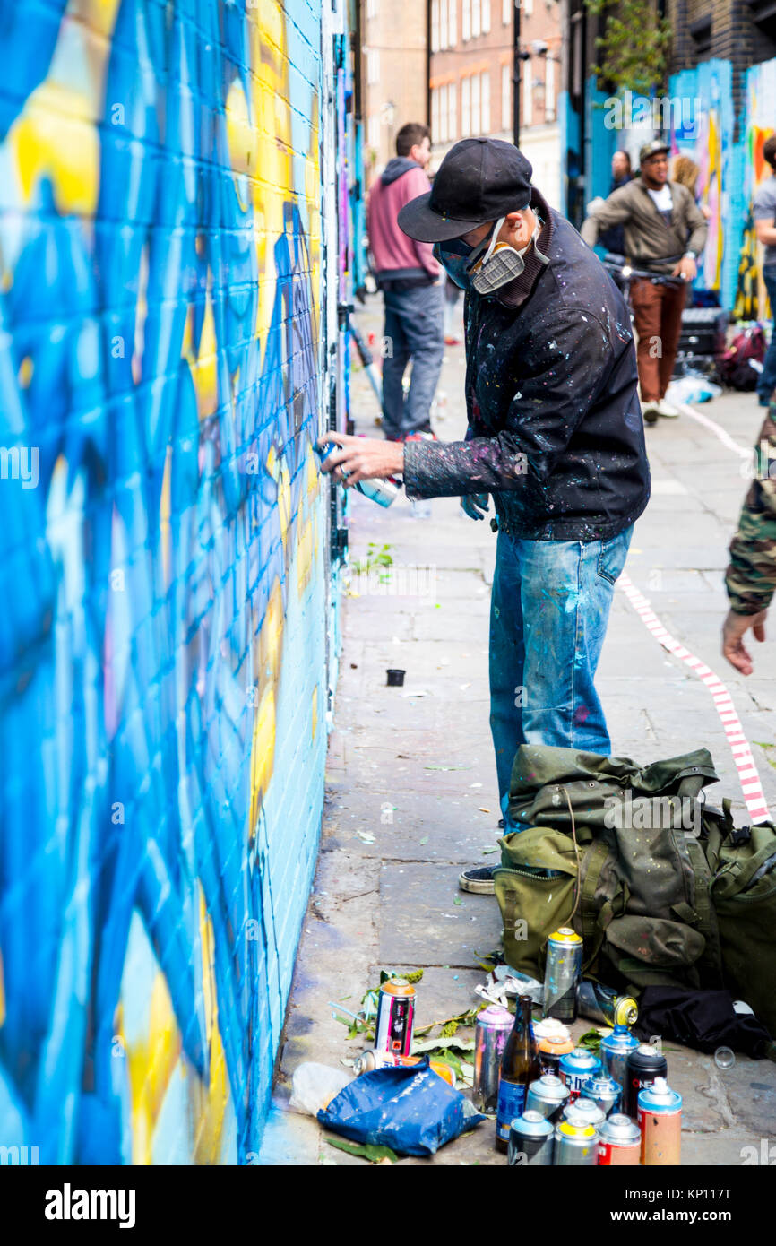Graffiti street artist wearing a respirator mask spraying the walls in Fleur Street, London, UK - Stock Image