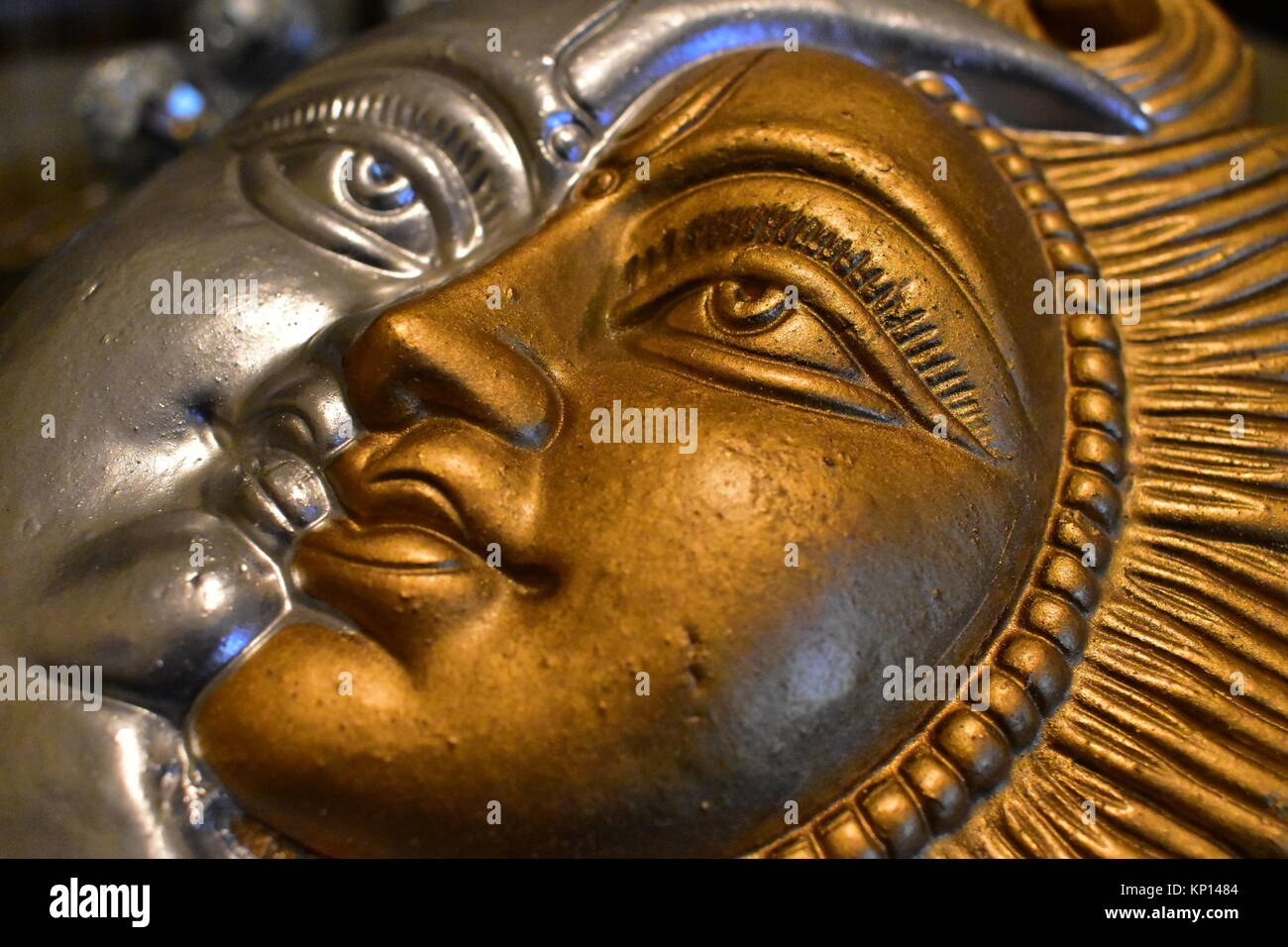 A golden and silver painted clay artifact symbolizing the sun and moon. Stock Photo