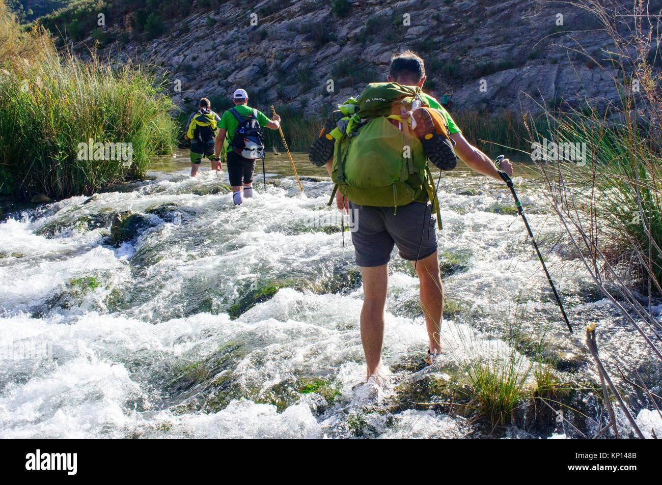 Walkers crossing the river Jucar in Millares, Valencia, Spain - Stock Image