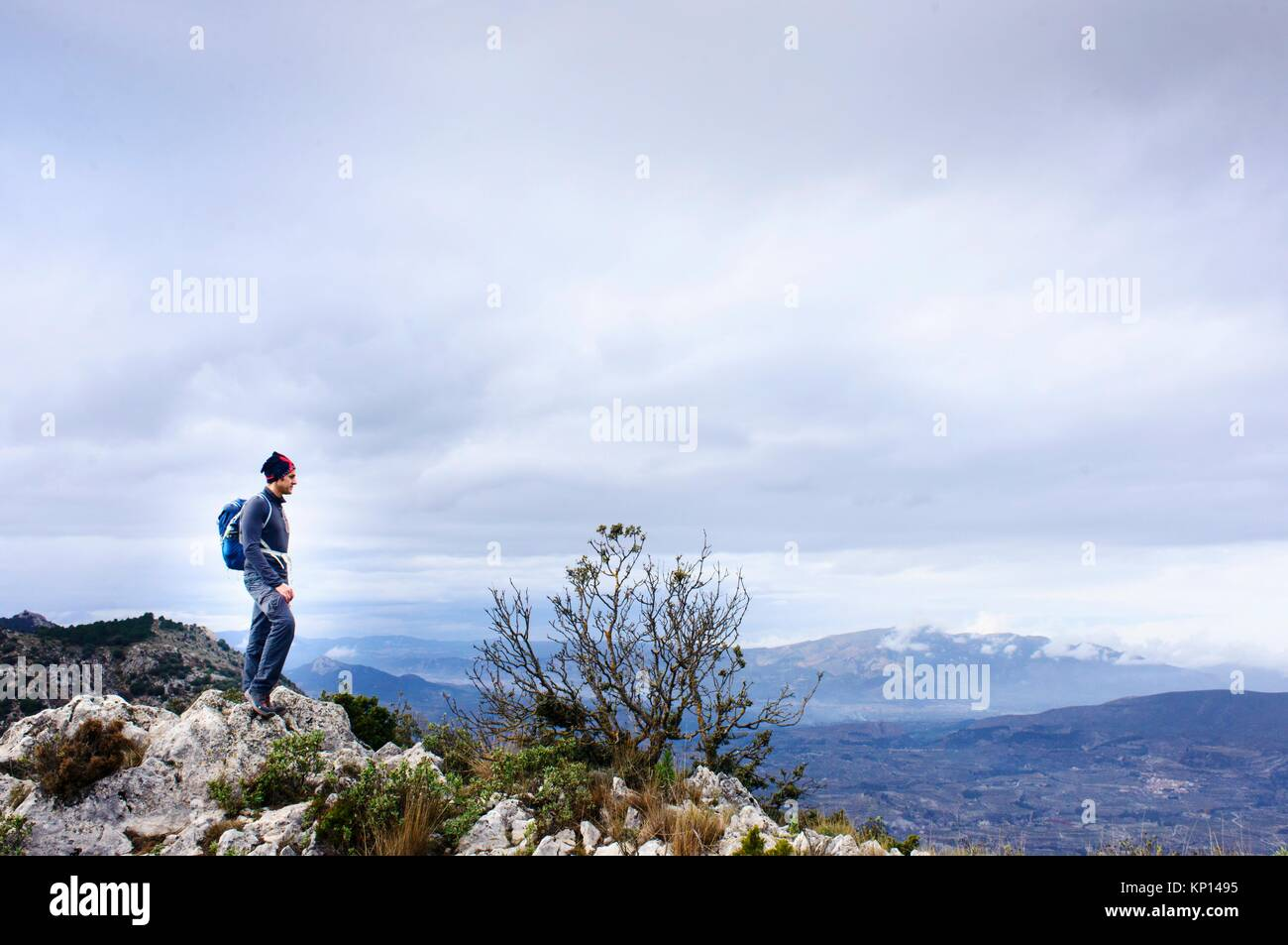 ountaineer on top of the mountain in Quatretondeta, Alicante, Valencia, Spain - Stock Image
