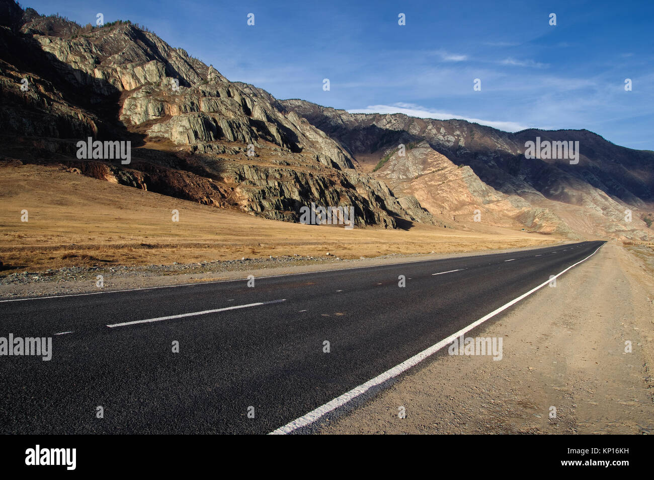 Road asphalt path on a desert wild mountain valley yellow dry grass at the background of the high ranges under a - Stock Image
